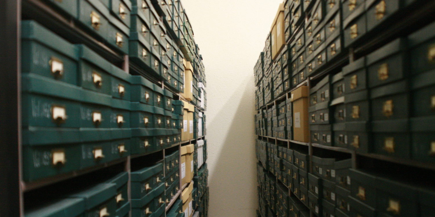 Stacks of archival boxes on shelves in the vault at the Mennonite Heritage Archives