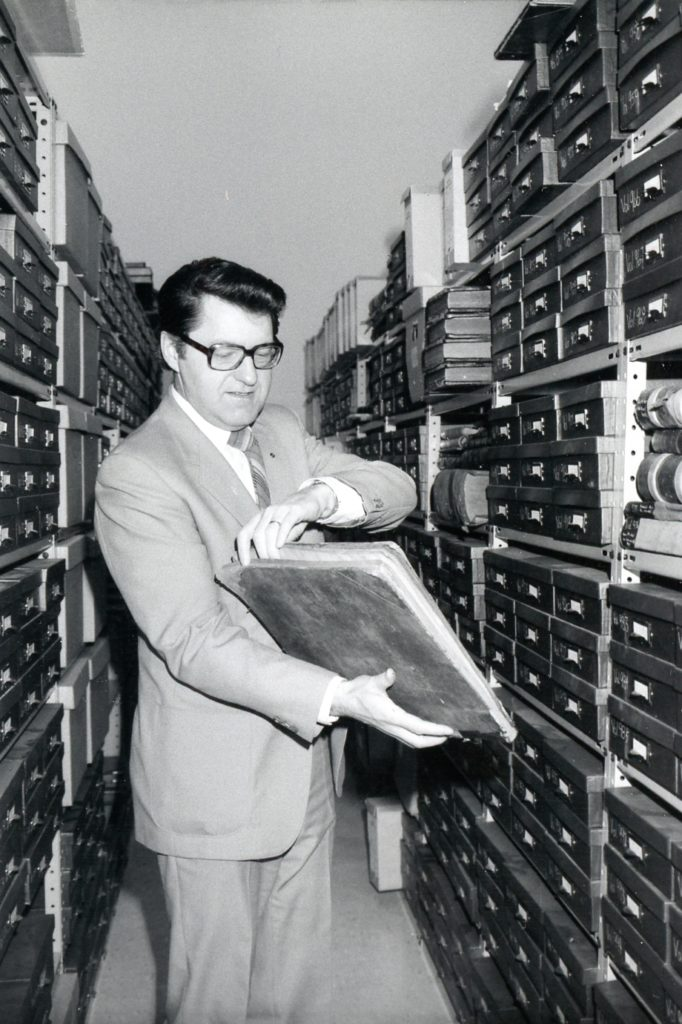 Lawrence Klippenstein looking at an old book in the vault of the Mennonite Heritage Archives in 1984